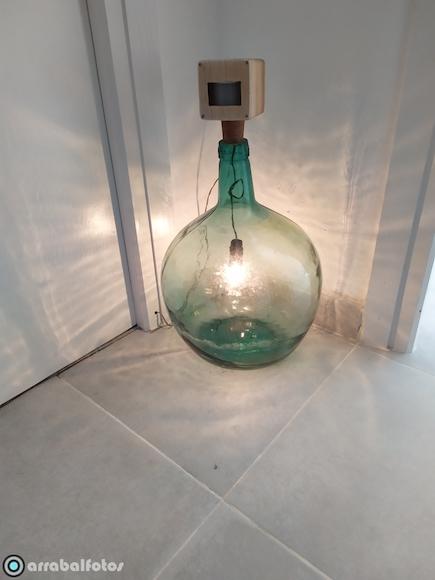 Lampara artesana hecha con materiales reciclados compuesta de damajuana y sensor para iluminar estancias de paso